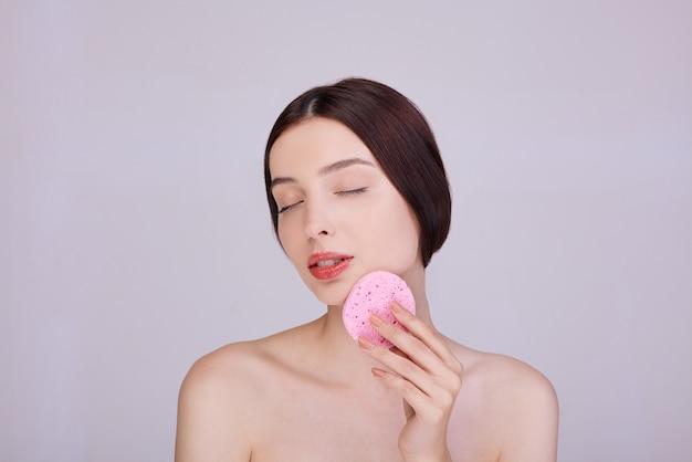 Prachtige brunette reinigt haar gezicht met een spons.