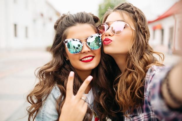 Prachtige brunette vriendinnen met kapsel, gespiegelde zonnebril en rode lippen maken selfie met eendgezicht.