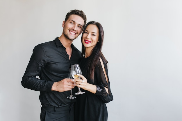 Prachtige brunette vrouw gerinkelglazen met knappe echtgenoot tijdens het feest van vriend