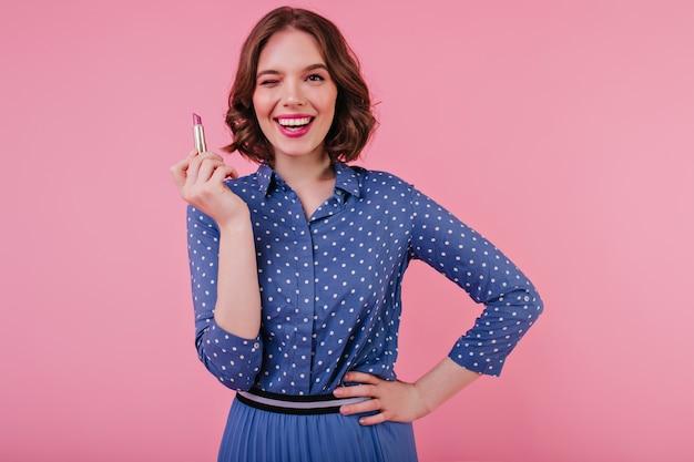 Prachtige brunette vrouw in blauw shirt poseren met nieuwe lippenstift. zelfverzekerd kaukasisch meisje met elegant kapsel dat zich op roze muur bevindt.