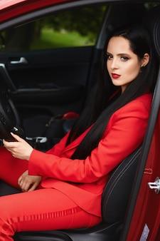 Prachtige brunette vrouw in een rood pak in de auto