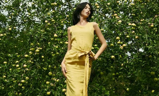 Prachtige brunette vrouw in mode gele jurk in een tuin
