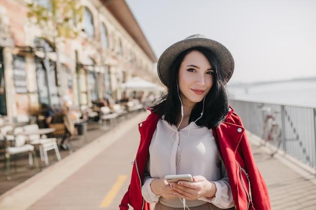 Prachtige brunette vrouw in oortelefoons tijd doorbrengen op kade