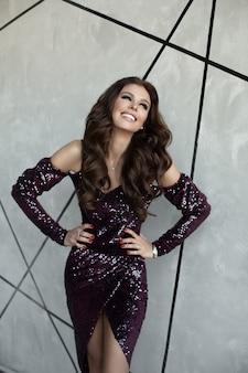 Prachtige brunette vrouw in sprankelende paarse jurk.