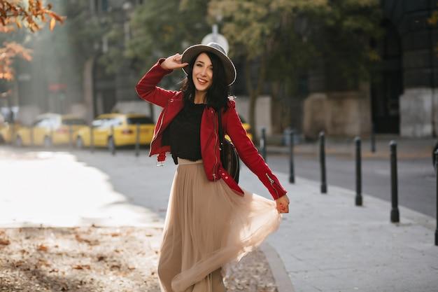 Prachtige brunette vrouw met charmante glimlach spelen met lange rok op stadsmuur