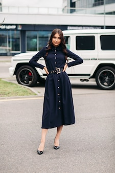 Prachtige brunette vrouw met lang golvend haar in een donkere jurk met knopen