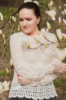 Prachtige brunette vrouw met naakte make-up, gekleed in kanten blouse, poserend in de buurt van de bloeiende magnoliabloemen