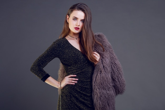 Prachtige brunette vrouw met rode lippen harige jas en cocktailjurk poseren dragen