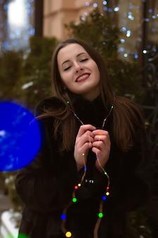 Prachtige brunette vrouw met zwarte bontjas, poseren met bloemenslinger in de winter