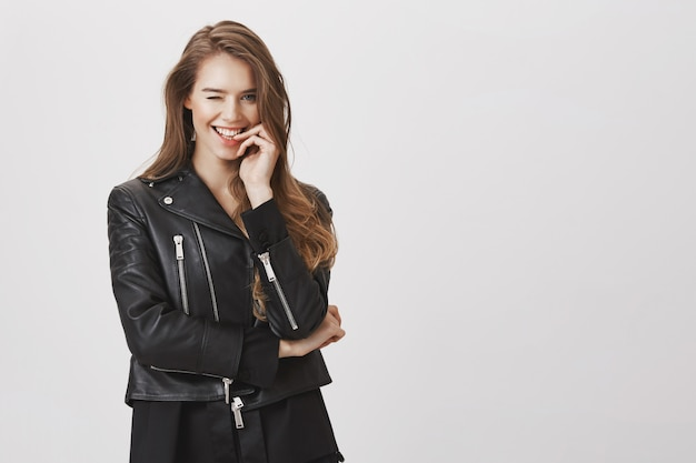 Prachtige brutale vrouw in leren jas, glimlachend en knipogen