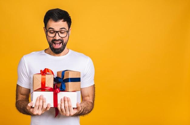 Prachtige cadeaus! schattige foto van aantrekkelijke bebaarde man met mooie glimlach met verjaardagsgeschenk dozen geïsoleerd op gele achtergrond.
