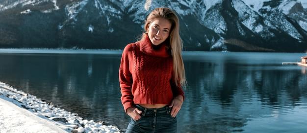Prachtige dame die buiten staat op de besneeuwde oever van het diepe meer en een prachtig uitzicht op de bergen. vrolijk meisje in oversized trui en spijkerbroek. geen make-up en lang blond kapsel. blauwe heldere hemel.