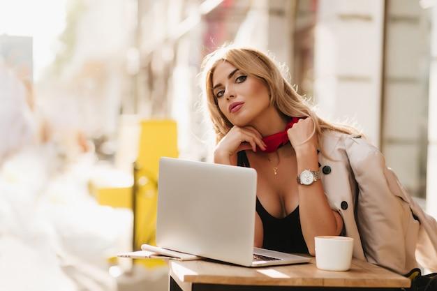 Prachtige dame draagt ketting en polshorloge kijkt naar camera tijdens het werk met laptop in café