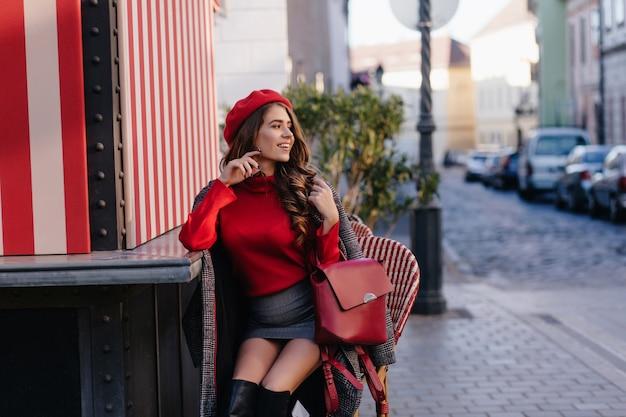 Prachtige dame draagt minirok zittend op terras met rode rugzak en rondkijken