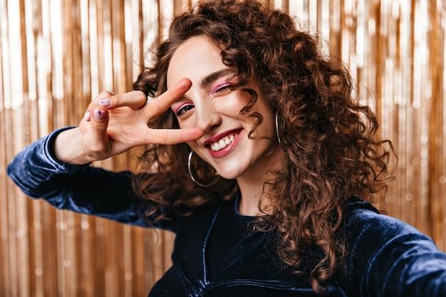 Prachtige dame in donkerblauwe bovenkant die vredesteken toont en selfie neemt