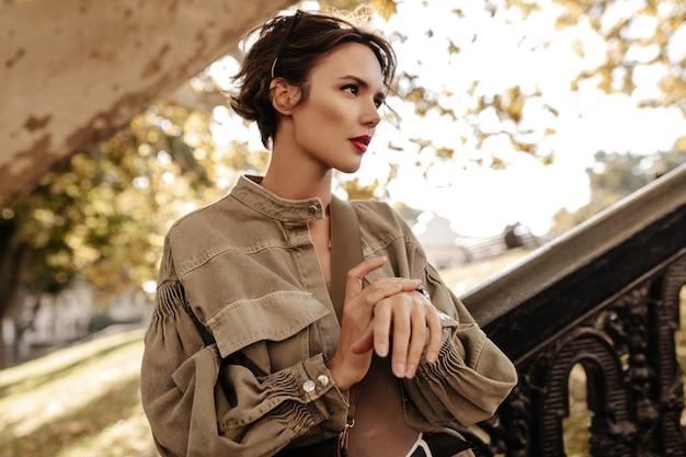 Prachtige dame in een wijde spijkerjas die naar buiten kijkt. trendy vrouw met kort krullend kapsel en heldere lippen poseren buitenshuis.