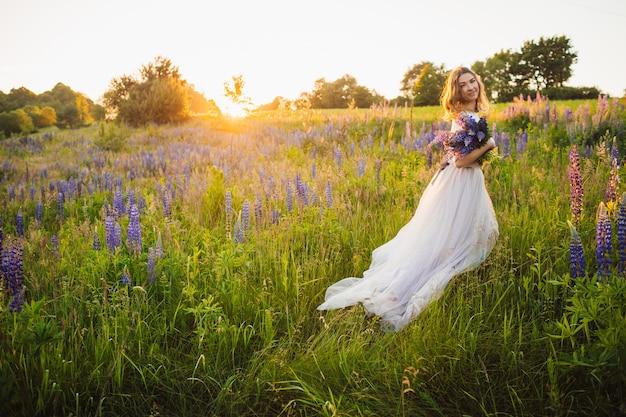 Prachtige dame in witte jurk staat met boeket op het veld