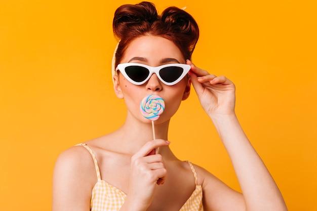 Prachtige dame in zonnebril harde snoep likken. vooraanzicht van pinup meisje met lolly geïsoleerd op gele ruimte.