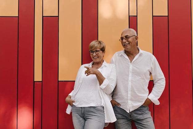 Prachtige dame met kort haar in lichte kleding en bril lachen met man met snor in witte kleren op rood en oranje.