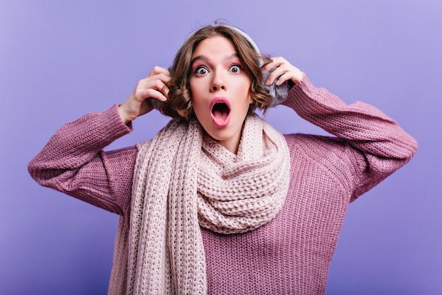 Prachtige donkerharige vrouw met grote ogen wat betreft haar vacht koptelefoon. geschokt bleek meisje in sjaal poseren met open mond.