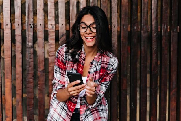 Prachtige donkerharige vrouw telefoonscherm kijken en lachen. openluchtportret van mooi latijns-meisje dat op houten muur met haar apparaat wordt geïsoleerd.