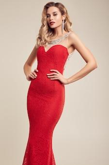 Prachtige elegante blonde vrouw mode rode jurk dragen