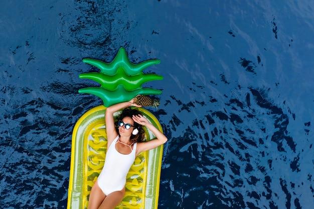 Prachtige europese vrouw in zwembroek liggend op ananasmatras. schattig slank meisje in zonnebril koelen in zwembad in zomerochtend.