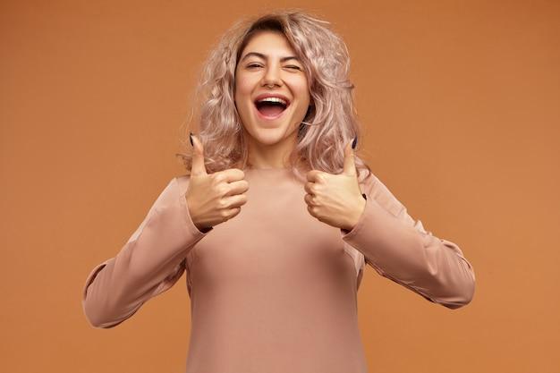Prachtige extatische tienermeisje met roze haren en neusring schreeuwen van opwinding en duimen omhoog gebaar maken, positieve emoties tonen
