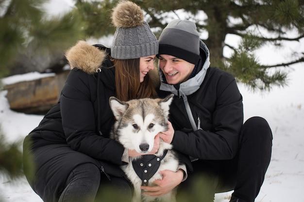 Prachtige familie, een man en een meisje in winter forest met hond. speel met de hond siberische husky.