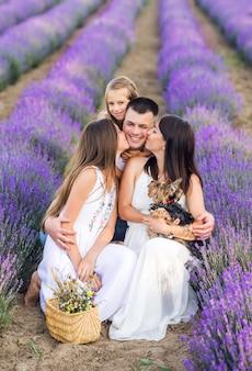 Prachtige familie en hun kleine hond in een lavendelveld. zomerfoto in paarse kleuren.