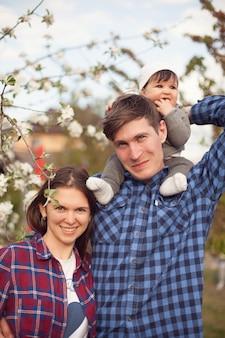 Prachtige familie in geruite overhemden tegen de achtergrond van een wit bloeiende appelboom
