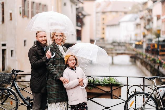 Prachtige familie met parasols bij regenachtig weer in annecy. frankrijk. familie wandeling in de regen.