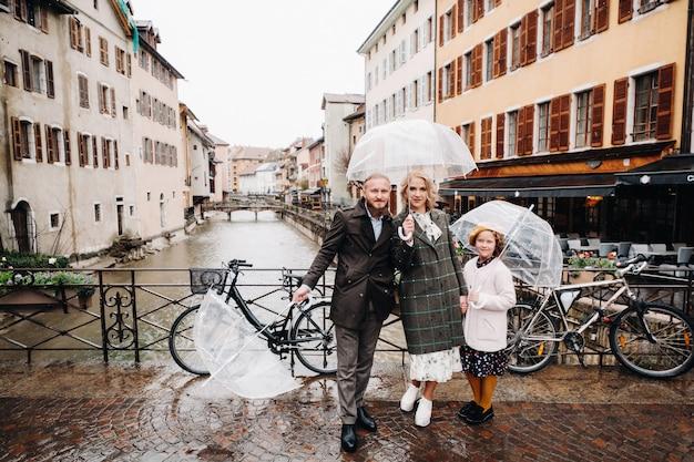 Prachtige familie met parasols bij regenachtig weer in annecy