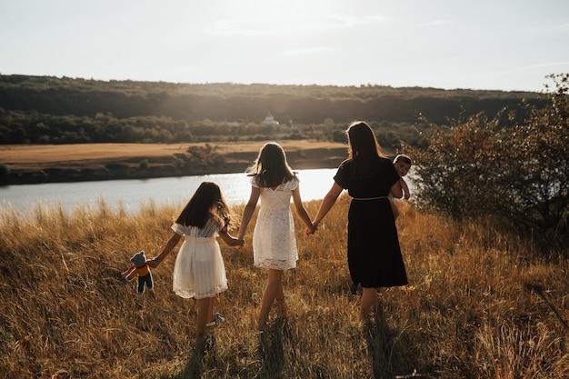 Prachtige familie wandelen op het strand van de rivier