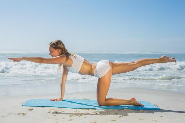 Prachtige fit blonde in pilates pose op het strand