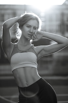 Prachtige fitness vrouw met perfect lichaam dragen sport kleding poseren op een tennisbaan in stralen van de zon. zwart-witte kleur