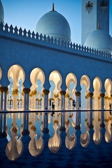 Prachtige galerij van de beroemde sheikh zayed white mosque in abu dhabi, verenigde arabische emiraten 's nachts Premium Foto