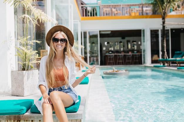 Prachtige gebruinde dame die met haar lange haar speelt terwijl ze in het zwembad poseert. blij vrouwelijk model in hoed die dichtbij water in weekend zonnebaadt.