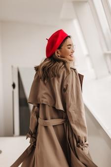 Prachtige gekrulde lichtharige vrouw in rode hoed en oversized beige trenchcoat loopt door de gang