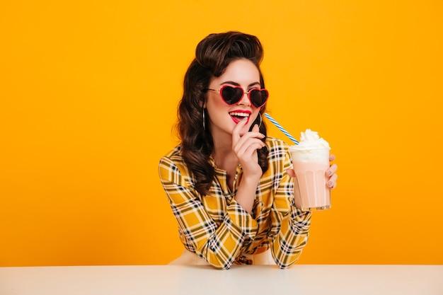 Prachtige gekrulde vrouw die van milkshake geniet. studio shot van pinup meisje met cocktail poseren op gele achtergrond.