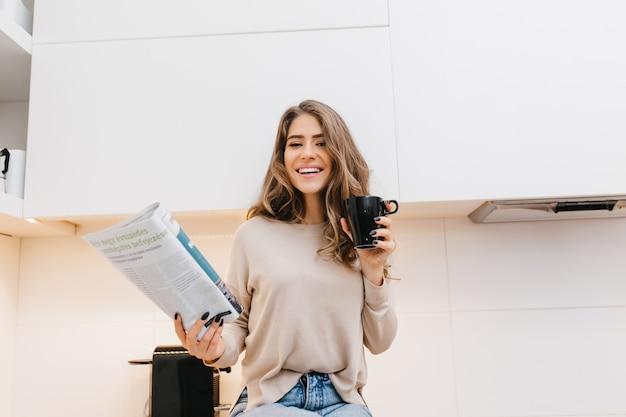 Prachtige gekrulde vrouw koffie drinken in de ochtend en poseren met tijdschrift