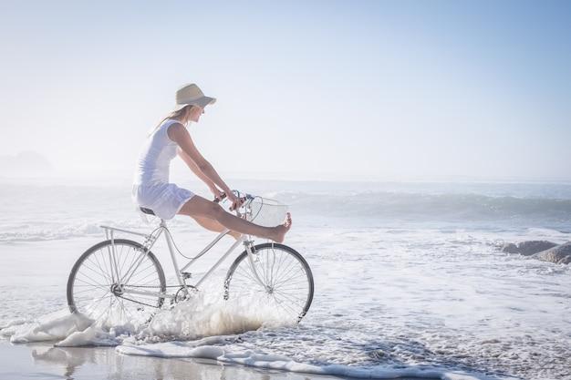 Prachtige gelukkige blonde op een fietstocht op het strand