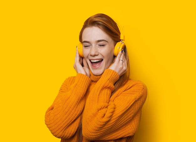 Prachtige gember kaukasische dame luistert naar muziek terwijl ze een trui draagt op een gele achtergrond met kopie ruimte