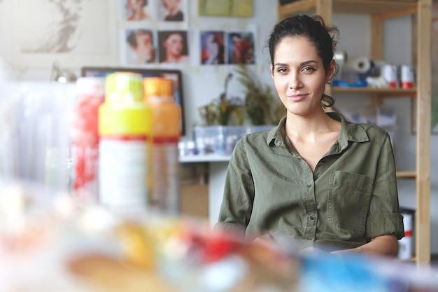 Prachtige getalenteerde student-vrouw met de wens om een goede kunstenaar te worden die vrije tijd doorbrengt in een universitaire workshop op zoek naar inspiratie