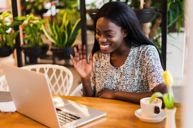 Prachtige glimlachende vrouw geniet van recreatie in de coffeeshop, heeft een videogesprek via draagbare laptop, maakt gebruik van de applicatie.