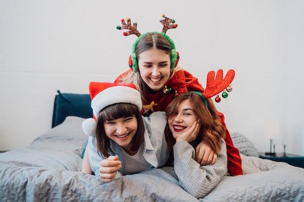 Prachtige glimlachende vrouwelijke modellen die pret hebben en van pyjama'spartij genieten