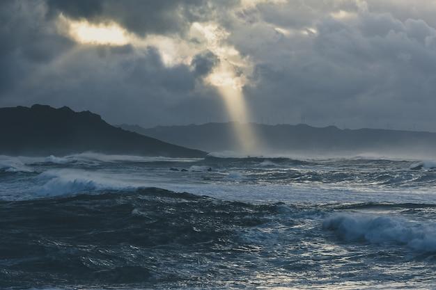 Prachtige golven van de stormachtige oceaan vastgelegd op een bewolkte avond