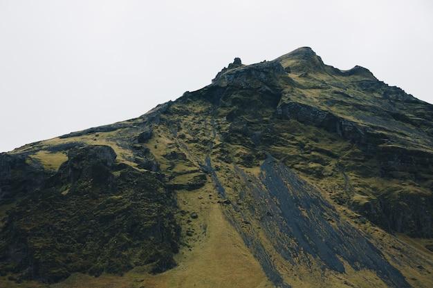 Prachtige groene steile heuvel met een heldere witte lucht op de achtergrond