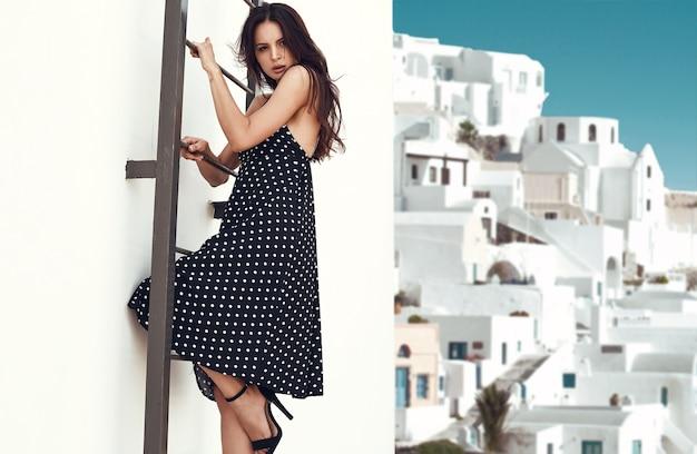 Prachtige heldere brunette in mode jurk klimt op de trap naar het dak