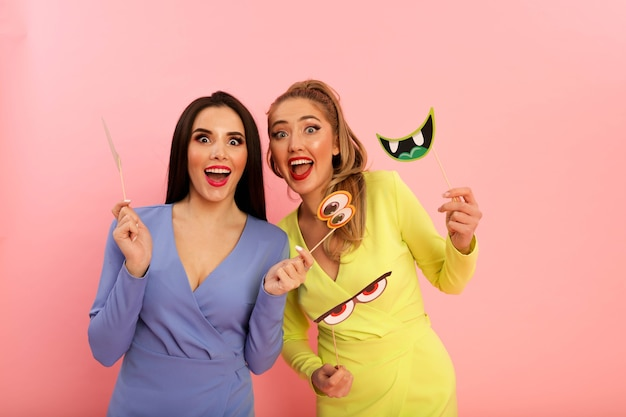 Prachtige heldere dames in stijlvolle zomerjurken, geel en blauw. blond en brunette met grote rode lippen en modern kapsel. welgevormde hete lichamen, sexy modellen. schieten in de studio op de achtergrond van de pin